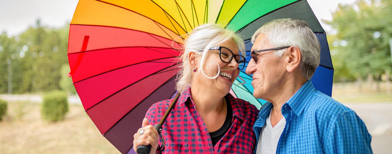 Ehepaar steht unter einem bunten Regenschirm in allen möglichen Farben.