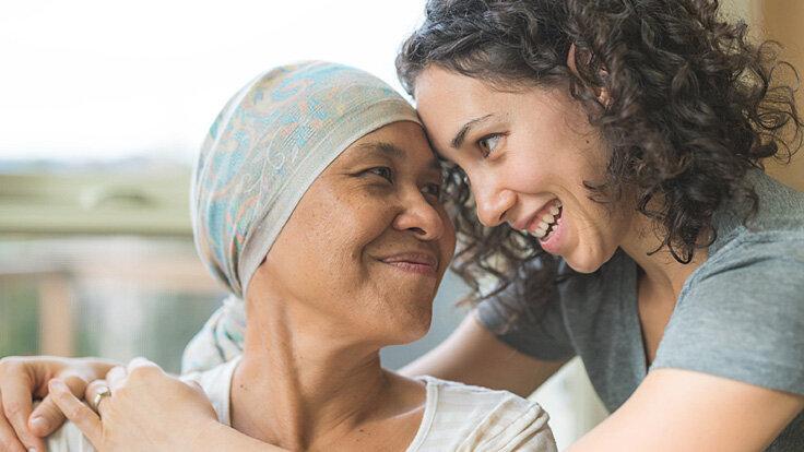 Junge Frau umarmt ihre krebskranke Angehörige, spendet Kraft und macht ihr Mut.