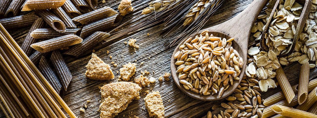 Auf einem Tisch liegt eine große Variation von Vollkorngetreideerzeugnissen wie ganze Körner, Vollkornnudeln und Haferflocken.