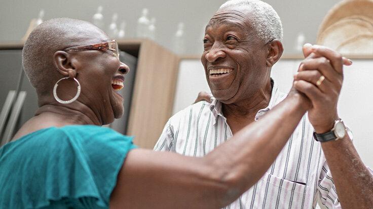 Ein älteres Paar hat das Empty Nest Syndrom überwunden und tanzt in der Küche.