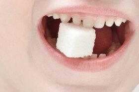 Kleiner Junge mit Würfelzucker im Mund - wieviel Zucker am Tag ist ok?