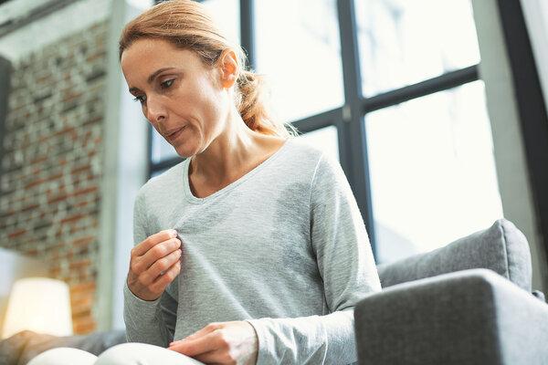 Eine Frau sitzt auf der Couch und hält sich das T-Shirt vom Körper, da sie von Wechseljahresbeschwerden geplagt wird.