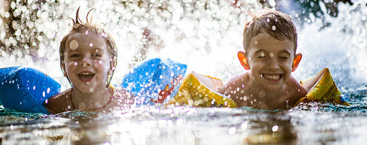 Zwei Kinder planschen im Wasser und tragen Schwimmflügel.