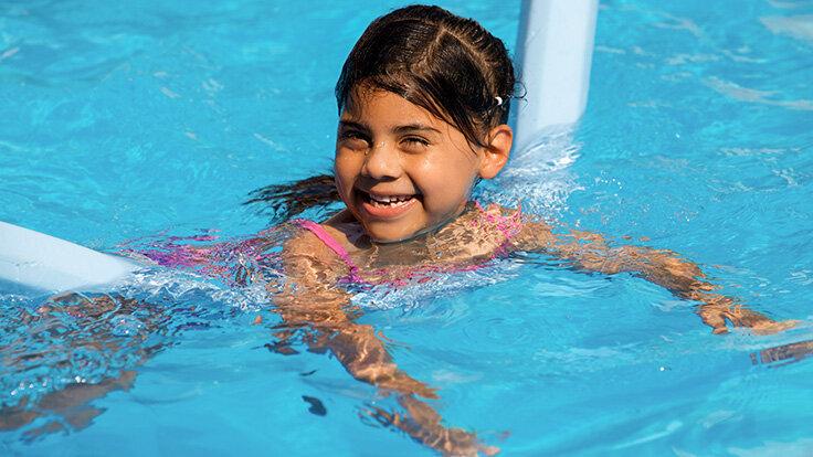 Ein Mädchen schwimmt im Pool mit einer Badenudel.