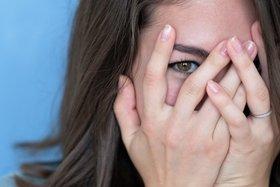 Brünette Frau schämt sich und hält ihre Hände vor das errötete Gesicht