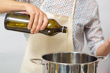 Eine Frau gibt Öl in einen Topf, um zu kochen.