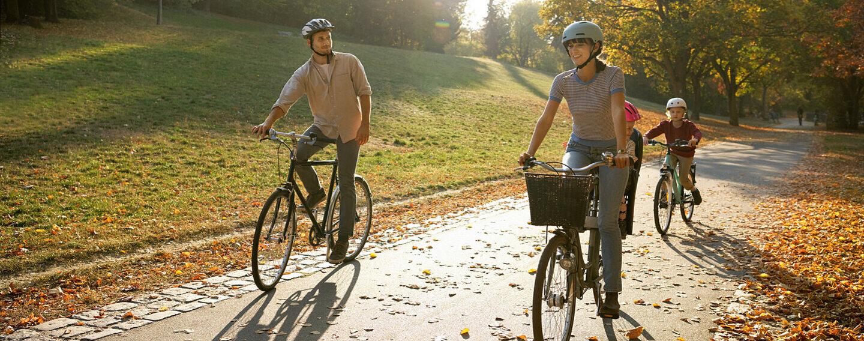 Ein Paar und ihre zwei Kinder fahren Fahrrad im Wald.