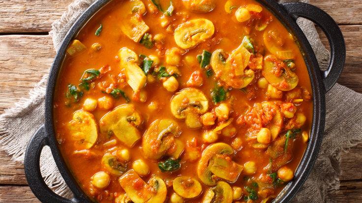 Rustikale Pilzsuppe mit Curry und Kichererbsen in einer schwarzen Pfanne.