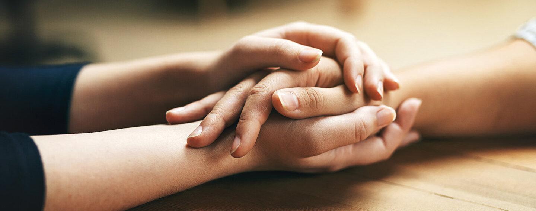 Zwei Menschen halten sich die Hände und unterstützen sich in der Trauer.