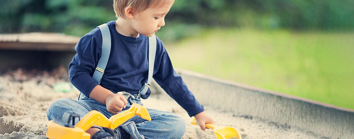 Ein Kind mit Autismus spielt konzentriert im Sandkasten.