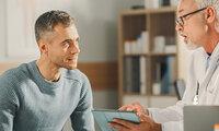 Ein junger Mann spricht mit seinem Arzt über Hodenkrebs.