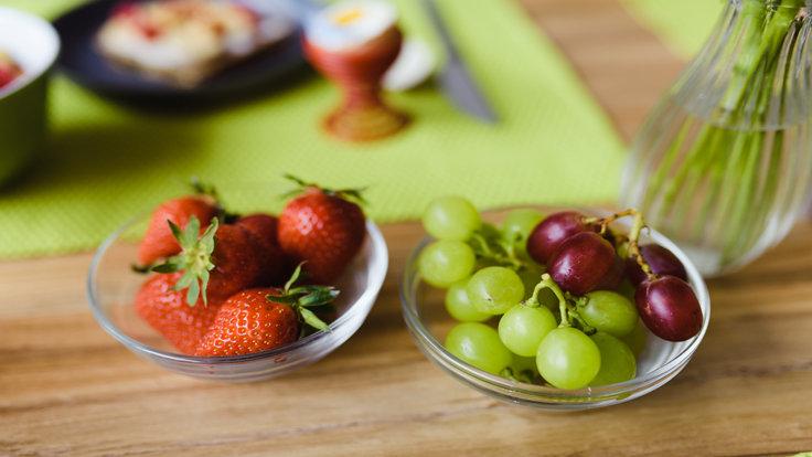 Erdbeeren und Trauben in einer Schale auf einem Frühstückstisch