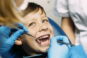 Ein Junge wird bei der zahnärztlichen Vorsorgeuntersuchung von einer Kinderzahnärztin behandelt.
