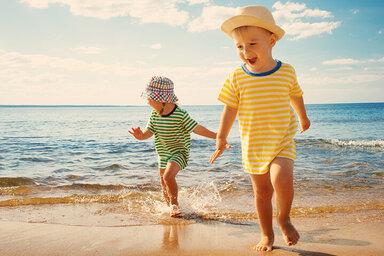 Zwei Kinder mit Sommerbekleidung toben am Strand