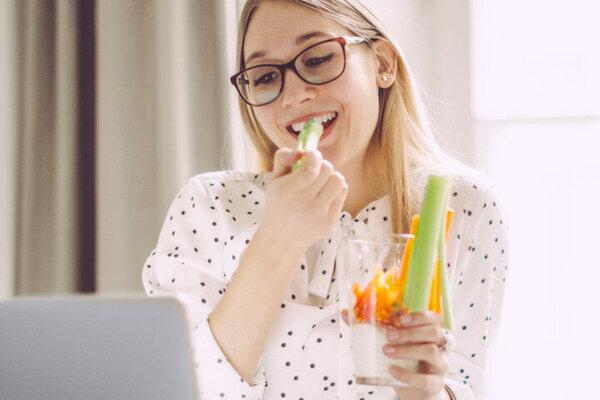 Junge Frau isst einen gesunden Low-Carb-Snack am Schreibtisch.