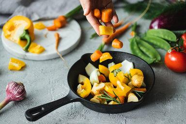 Obst und Gemüse liegen auf einem Tisch mit einem Schneidebrett.