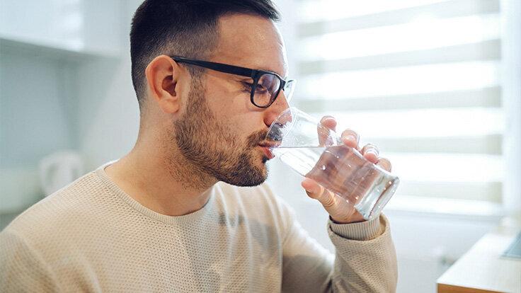 Ein Mann trinkt stilles Wasser aus einem Glas