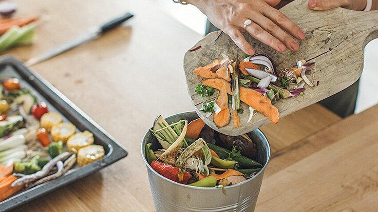 Eine Frau sortiert Reste zum Kompostieren.