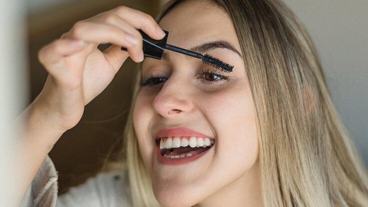 Eine Frau gibt mit einem Wattestäbchen Wimpernserum auf ihre Wimpern