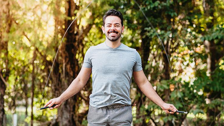 Ein Mann macht Seilspringen im Park – so geht Cardio Training.