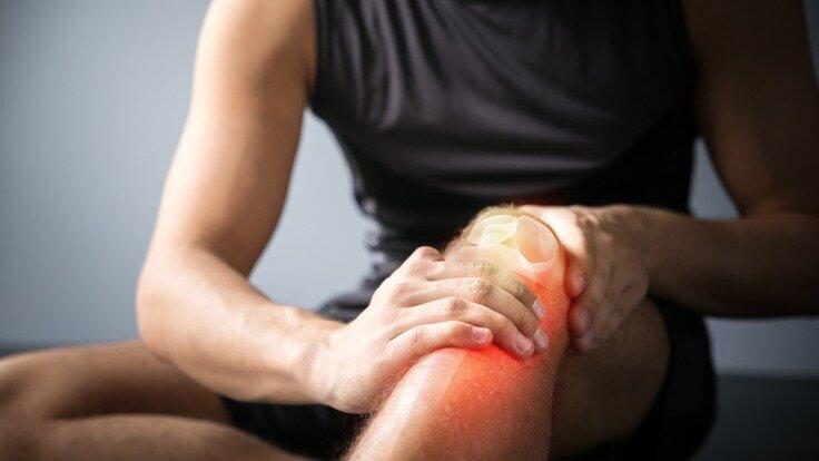 Ein Mann in Sportkleidung fasst sich ans Knie
