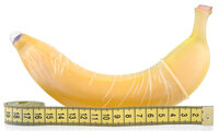 Banane mit übergezogenem Kondom neben einem Maßband