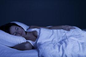 Einschlafhilfe: Eine junge Frau schläft entspannt in einem abgedunkelten Raum mit einem stützenden Kissen unter dem Kopf.