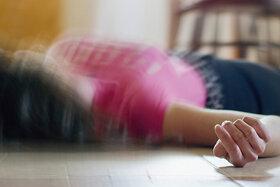Eine Frau liegt mit einem epileptischen Anfall auf dem Boden