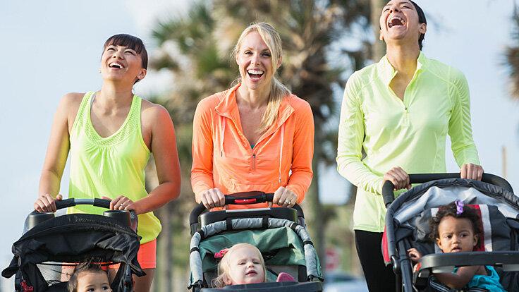 Drei junge Mütter gehen mit einem Baby-Jogger und ihren Kindern laufen.