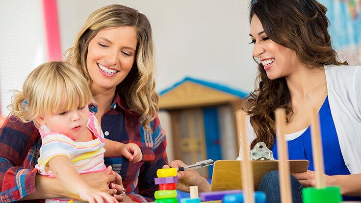 Mutter und Erzieherin sprechen über Eingewöhnung der Tochter.