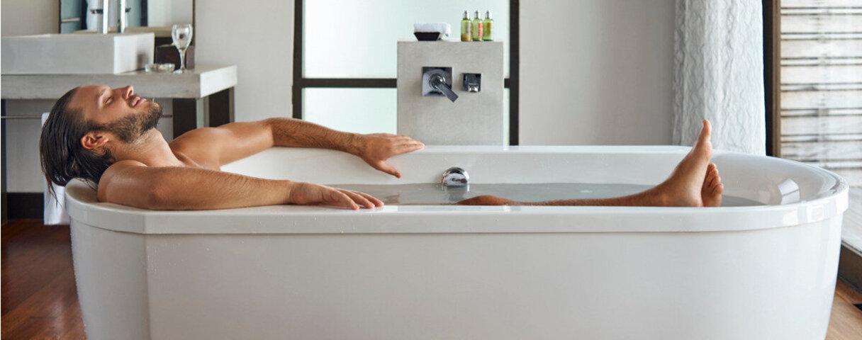 Wellness zu Hause: Mann liegt in der Badewanne.