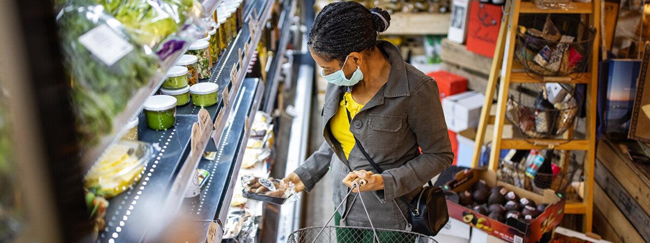 Frau steht beim Einkaufen vor dem Kühlregal und vergleicht Nährwerte von Produkten miteinander.