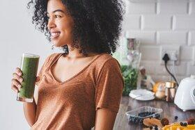 Eine Frau hält einen Smoothie mit vielen Vitaminen in der Hand.