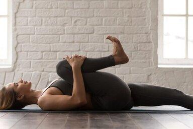 Frau übt Progressive Muskelentspannung im Liegen auf einer Matte