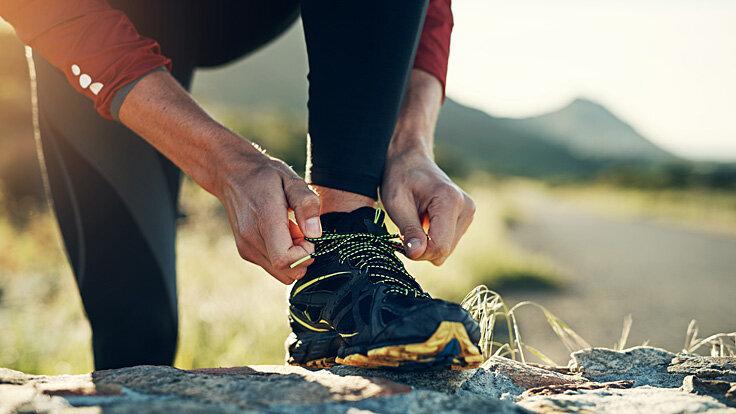 Ein Mann bindet sich die Schnürsenkel seiner Laufschuhe zu.