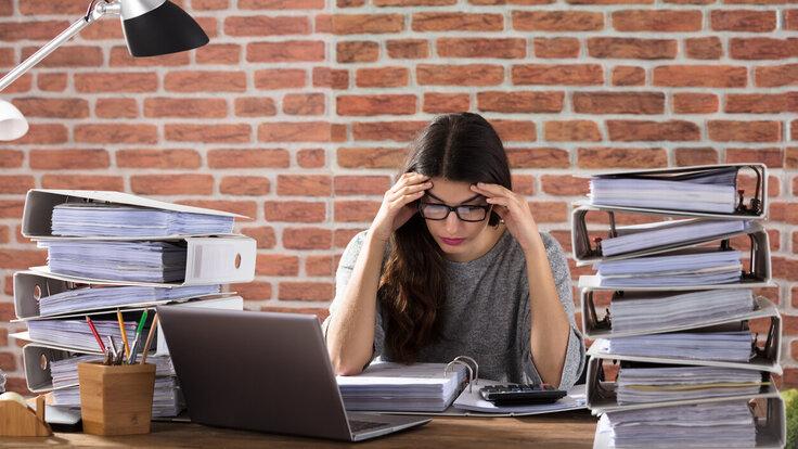 Eine Frau sitzt mit Kopfschmerzen zwischen Aktenbergen am Schreibtisch.