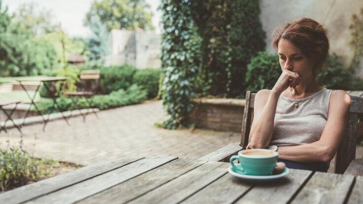 Depressive Frau sitzt am Tisch mit Kaffeebecher