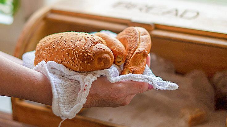 Frau bewahrt Brot und Brötchen im Brotkasten auf, weil sie weiß, dass beides länger frisch bleibt.