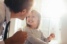 Kind hat die Zähne geputzt und zeigt sie seinem Vater