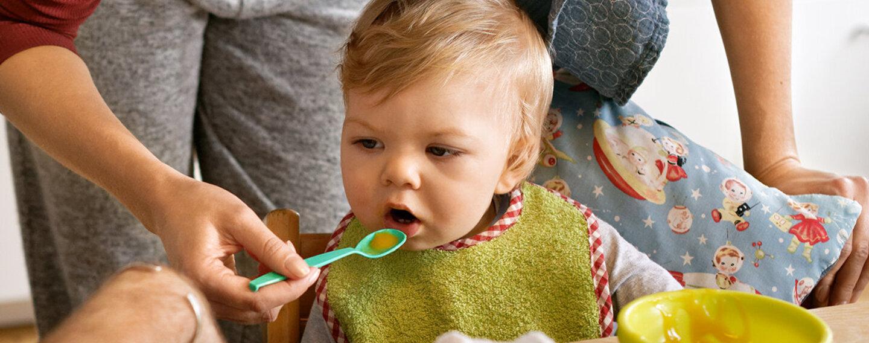 Eltern legen Wert auf eine gesunde Ernährung für Kinder und füttern ihr Baby mit frischem Brei.