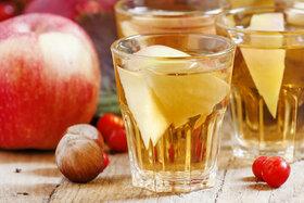 Punsch-Gläser neben Äpfeln auf einem Tisch.