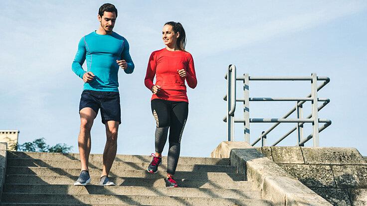 Ein Mann und eine Frau joggen eine Treppe runter.