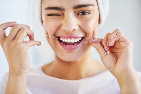 Eine Frau reinigt ihre Zähne mit Zahnseide.