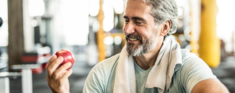 Ein Mann isst nach dem Sport einen Apfel.