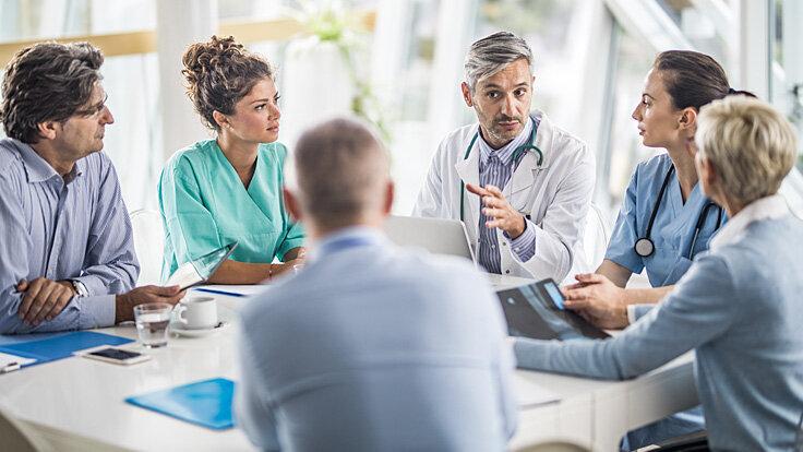 Ein Team aus Ärzten sitzt an einem Tisch und bespricht einen Fall von chronischen Schmerzen.
