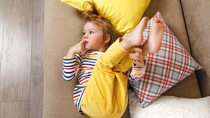 Ein Kind mit Schwindel hält die Füße hoch.