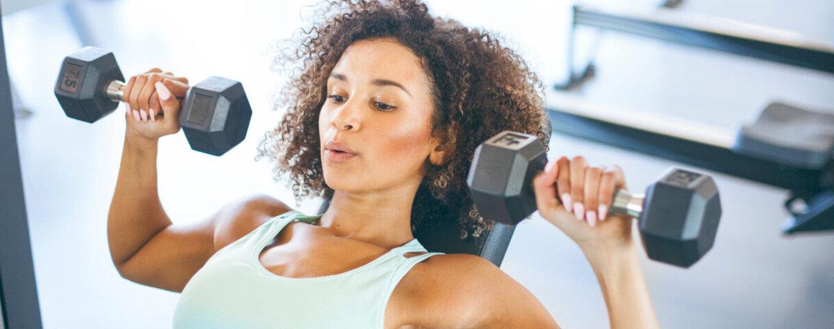 Frau treibt Hantelsport als guten Vorsatz, mehr Sport zu betreiben.
