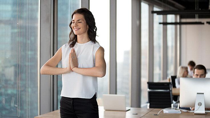 Junge Frau dehnt ihre Handgelenke und macht Übungen im Büro, um einem Mausarm präventiv vorzubeugen.