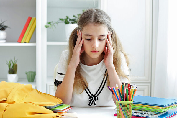 Ein Mädchen sitzt am Schreibtisch und hält ihre Hände an die Schläfen, da es unter Schwindel leidet.