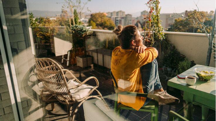 Single-Frau sitzt auf dem Balkon und blickt in die Ferne.
